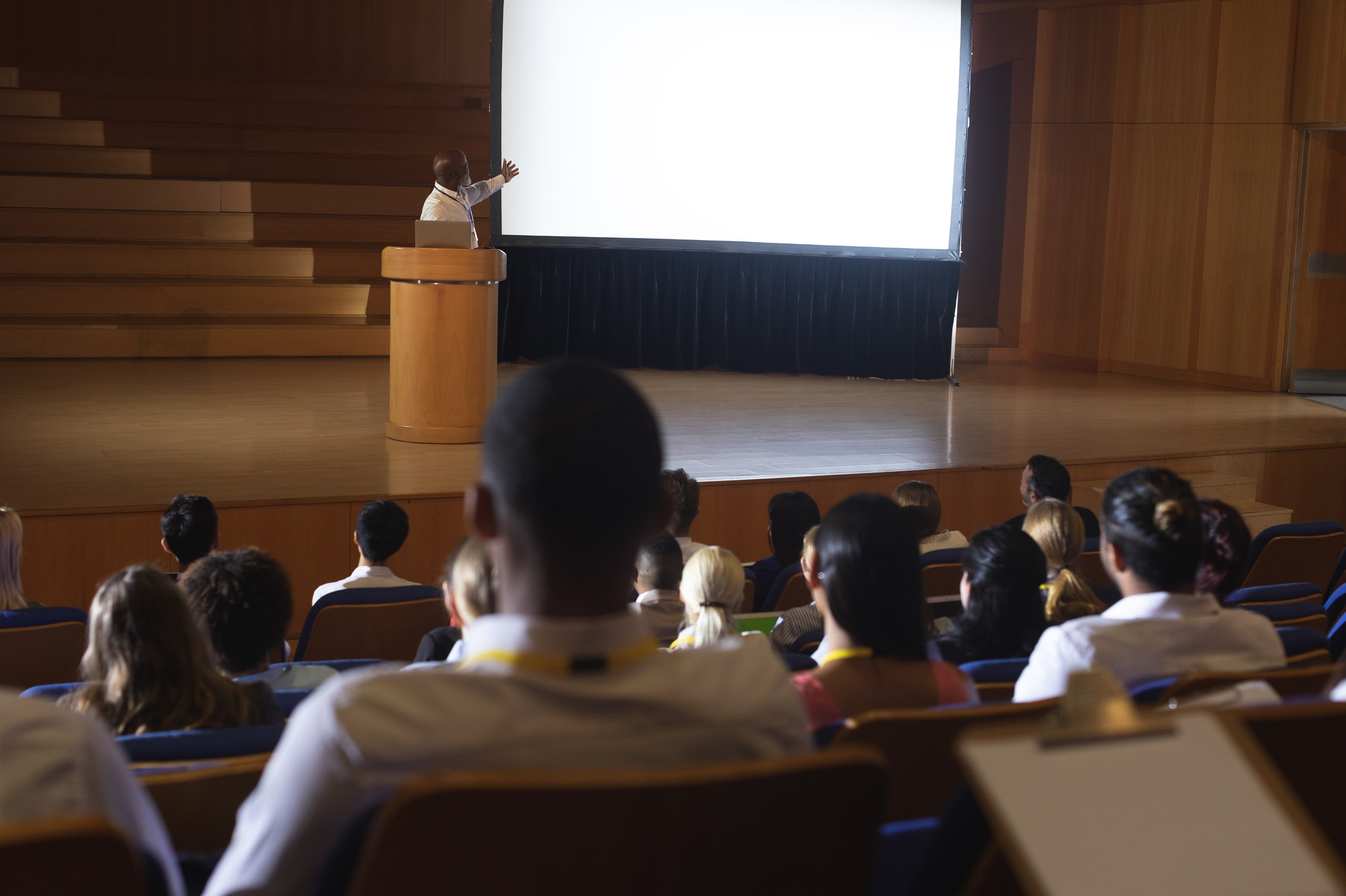 Businessman standing around podium and giving presentation in the auditorium